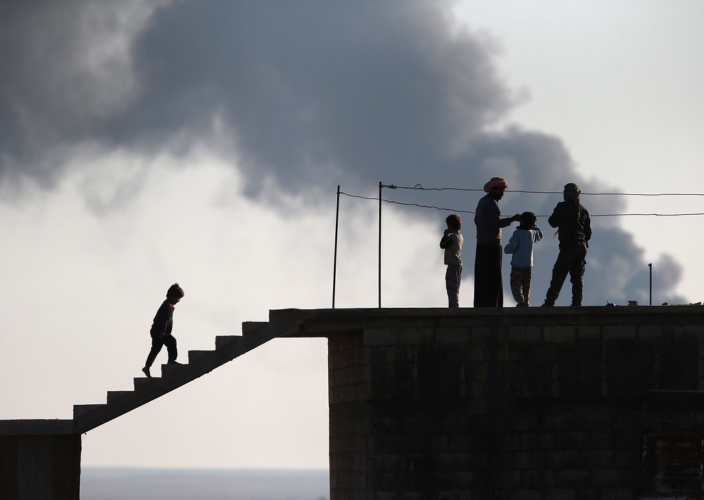 . Local residents speak with a Kurdish soldier while an oil well burns in the distance on November 10, 2015 near the ISIL-held town of Hole in the autonomous region of Rojava, Syria. Troops from the Syrian Democratic Forces, a coalition of Kurdish and Arab units, are attacking ISIL extremists in the area near the Iraqi border. The predominantly Kurdish region of Rojava in northern Syria has become a bulwark against the Islamic State. Their armed forces, with the aid of U.S. airstrikes and weapons, have been battling ISIL, who had earlier captured much of the region from the Syrian regime.  (Photo by John Moore/Getty Images)