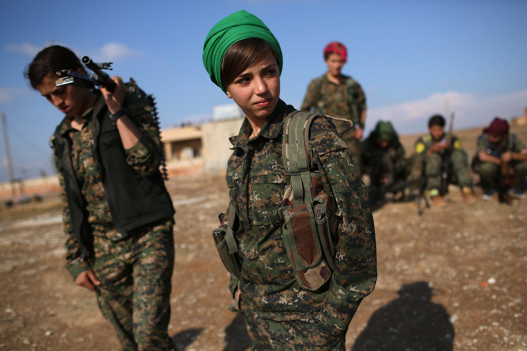 . Kurdish female troops from the Syrian Democratic Forces stand in a forward operating base overlooking the frontline on November 10, 2015 near the ISIL-held town of Hole in the autonomous region of Rojava, Syria. The forces, primarily Kurdish, are attacking ISIL extremists in the area near the Iraqi border and calling in airstrikes from U.S.-led coalition warplanes. The autonomous region of Rojava in northern Syria has become a bulwark against the Islamic State. The Rojava armed forces, with the aid of U.S. airstrikes and weapons, are retaking territory which had earlier been captured much by ISIL from the Syrian regime.  (Photo by John Moore/Getty Images)
