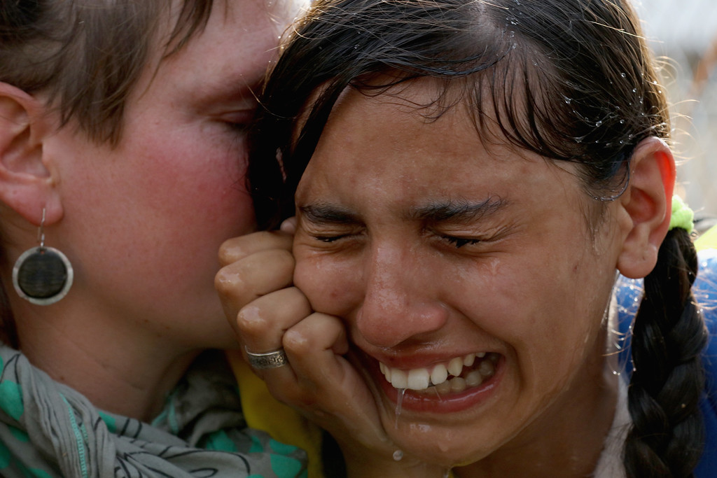 . A migrant girl is overcome by pepper spray and tear gas after Hungarian police repelled an attempt by migrants to break the border post gate and pull down the razor wire fence on September 16, 2015 in Horgos, Serbia. Hungary has introduced tough new laws to administer the influx of migrants and has declared a state of emergency in two of it\'s counties close to the border. The new laws have created a dead end for migrants arriving at the Horgos frontier post, resulting in clashes with migrants and Hungarian police.  (Photo by Christopher Furlong/Getty Images)