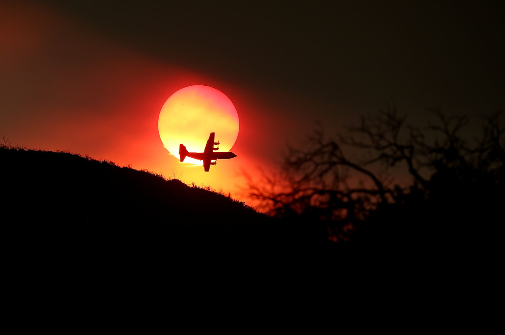 . A firefighting air tanker flies in front of the setting sun while battling the Rocky Fire on August 1, 2015 near Clearlake, California. Over 1,900 firefighters are battling the Rocky Fire that burned over 22,000 acres since it started on Wednesday afternoon. The fire is currently five percent contained and has destroyed at least 14 homes.  (Photo by Justin Sullivan/Getty Images)