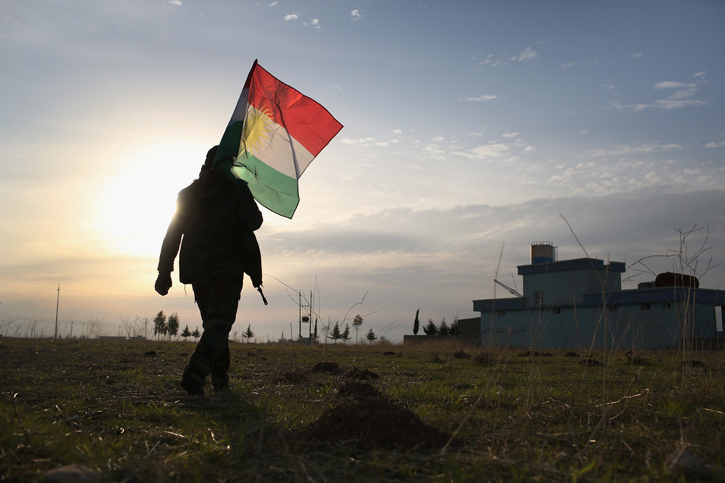 . A Peshmerga soldier walk to place a Kurdish flag near the frontline with ISIL on November 16, 2015 in Sinjar, Iraq. Kurdish forces, with the aid of massive U.S.-led coalition airstrikes, liberated the town from ISIL extremists, known in Arabic as Daesh, in recent days. Although many minority Yazidis celebrated the victory, their home city of Sinjar lay in almost complete ruins.  (Photo by John Moore/Getty Images)