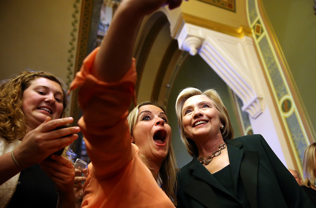 . Democratic presidential hopeful and former Secretary of State Hillary Clinton (R) stops to take a selfie after meeting with members of the Iowa State legislature at the Iowa State Capital on April 15, 2015 in Des Moines, Iowa. Hillary Clinton continues to campaign throughout Iowa as she makes her second bid for President of the United States.  (Photo by Justin Sullivan/Getty Images)