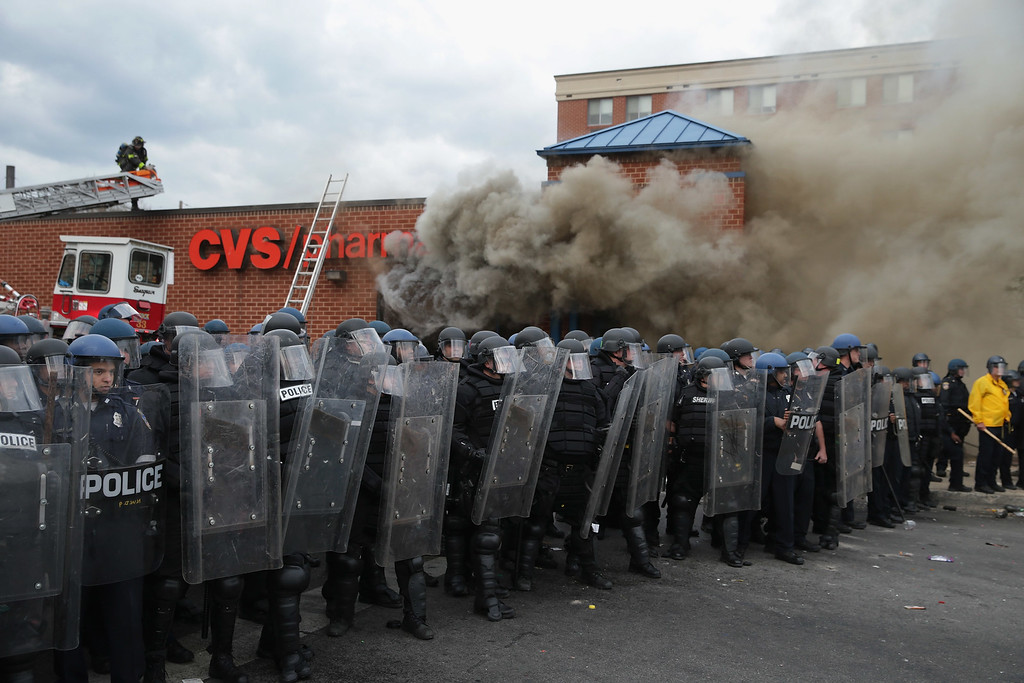 . Baltimore Police form a perimeter around a CVS pharmacy that was looted and burned near the corner of Pennsylvania and North avenues during violent protests following the funeral of Freddie Gray April 27, 2015 in Baltimore, Maryland. Gray, 25, who was arrested for possessing a switch blade knife April 12 outside the Gilmor Homes housing project on Baltimore\'s west side. According to his attorney, Gray died a week later in the hospital from a severe spinal cord injury he received while in police custody.  (Photo by Chip Somodevilla/Getty Images)
