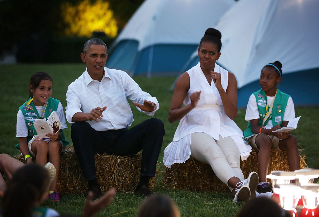 . U.S. President Barack Obama (2nd L) and first lady Michelle Obama (3rd L), flanked by Daphnye Shell (L) of Peggs, Oklahoma, and Kennedi Pridget (R) of Maryland, participate in a campfire songs session with fourth-grade Girl Scouts during the first-ever White House Campout June 30, 2015 at South Lawn of the White House in Washington, DC. The first lady hosted the event, as part of her Let\'s Move! Outside initiative, for Girl Scouts to participate in activities to earn their Camper Badge, and to celebrate the release of the new Girls\' Choice Outdoor badges.  (Photo by Alex Wong/Getty Images)