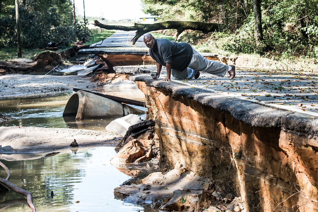 . Trey McMillian looks over the damage done by flood waters on a road in Eastover on October 6, 2015 in Eastover, South Carolina. The state of South Carolina experienced record rainfall amounts over the weekend and continues to face resulting flooding. (Photo by Sean Rayford/Getty Images)