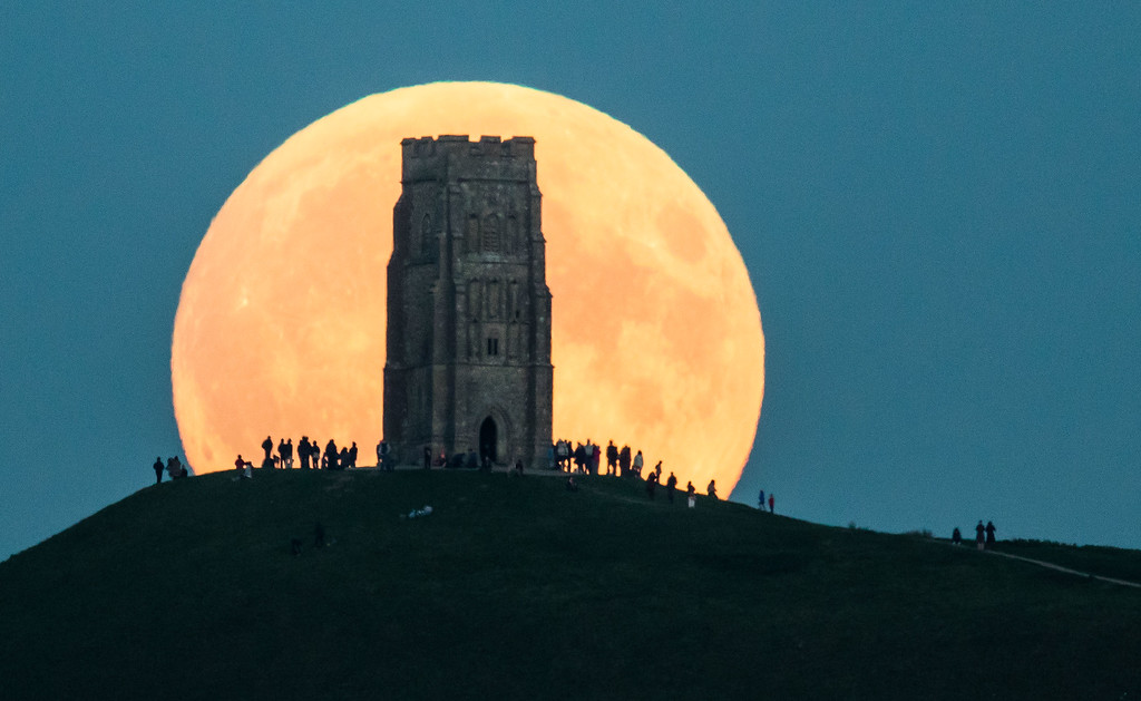 . The supermoon rises behind Glastonbury Tor on September 27, 2015 in Glastonbury, England. Tonight\'s supermoon, so called because it is the closest full moon to the Earth this year, is particularly rare as it coincides with a lunar eclipse, a combination that has not happened since 1982 and won\'t happen again until 2033.  (Photo by Matt Cardy/Getty Images)
