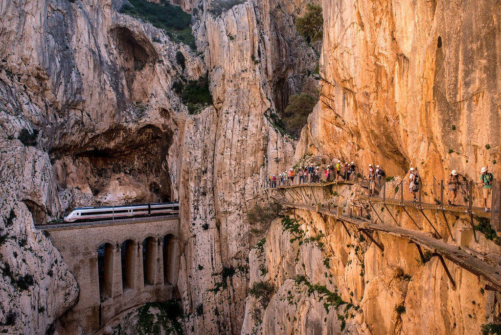 . A train passes through a tunnel as tourists walk along the \'El Caminito del Rey\' (King\'s Little Path) footpath on April 1, 2015 in Malaga, Spain. \'El Caminito del Rey\', which was built in 1905 and winds through the Gaitanes Gorge, reopened last weekend after a safer footpath was installed above the original. The path, known as the most dangerous footpath in the world, was closed after two fatal accidents in 1999 and 2000. The restoration started in 2011 and reportedly cost 5.5 million euros.  (Photo by David Ramos/Getty Images)