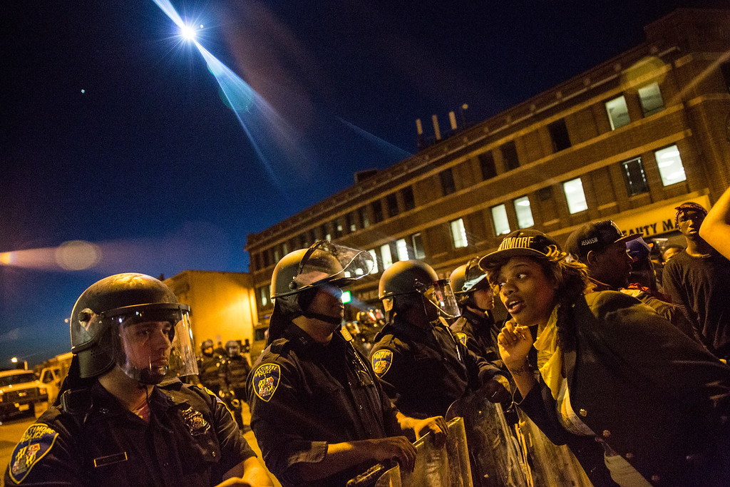 . A helicopter with a spot light watches over police and protesters before a mandatory, city-wide curfew of 10 p.m. near the CVS pharmacy that was set on fire yesterday during rioting after the funeral of Freddie Gray, on April 28, 2015 in Baltimore, Maryland. Gray, 25, was arrested for possessing a switch blade knife April 12 outside the Gilmor Houses housing project on Baltimore\'s west side. According to his attorney, Gray died a week later in the hospital from a severe spinal cord injury he received while in police custody.  (Photo by Andrew Burton/Getty Images)