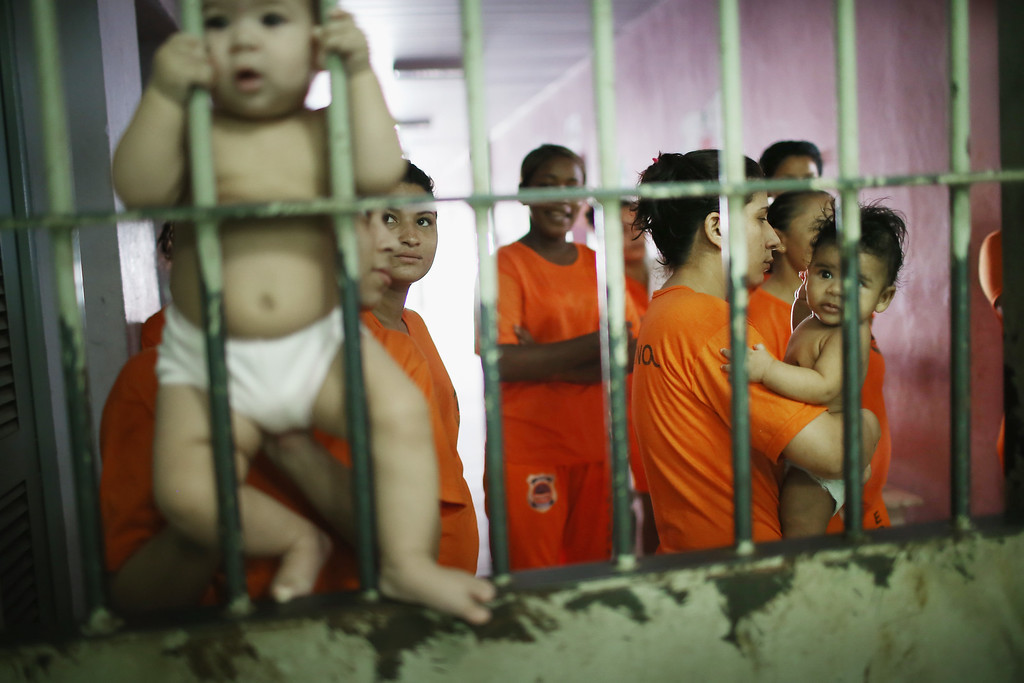 . Female inmates gather with babies as they greet visitors in the Pedrinhas Prison Complex, the largest penitentiary in Maranhao state, on January 27, 2015 in Sao Luis, Brazil. Previously one of the most violent prisons in Brazil, Pedrinhas has seen efforts from a new state administration, new prison officials and judiciary leaders from Maranhao which appear to have quelled some of the unrest within the complex. In 2013, nearly 60 inmates were killed within the complex, including three who were beheaded during rioting. Much of the violence stemmed from broken cells allowing inmates and gang rivals to mix in the patios and open spaces of the complex. Officials recently repaired and repopulated the cells allowing law enforcement access and decreasing violence among prisoners, according to officials. Other reforms include a policy of custody hearings and real-time camera feeds. According to officials there have been no prisoner on prisoner killings inside the complex in nearly four months. Critics believe overcrowding is one of the primary causes of rioting and violence in Brazil\'s prisons. Additionally, overcrowding has strengthened prison gangs which now span the country and control certain peripheries of cities including Rio de Janeiro, Sao Paulo and Sao Luis. Brazil now has the fourth-largest prison population in the world behind the U.S., Russia and China. The population of those imprisoned had quadrupled in the past twenty years to around 550,000 and the country needs at least 200,000 new incarceration spaces to eliminate overcrowding. A vast increase in minor drug arrests, a dearth of legal advice for prisoners and a lack of political will for new prisons have contributed to the increases.  (Photo by Mario Tama/Getty Images)