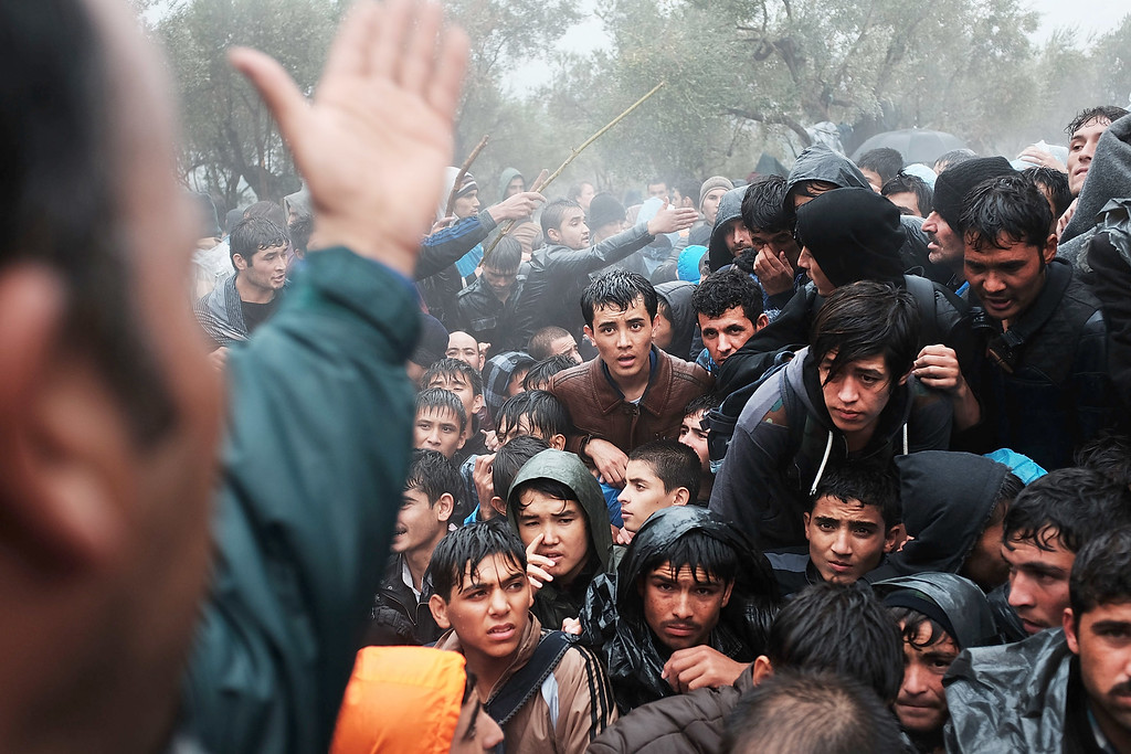 . Afghan men argue outside of the main gate as violence escalates for migrants waiting to be processed at the increasingly overwhelmed Moria camp on the island of Lesbos on October 22, 2015 in Mytilene, Greece. Dozens of rafts and boats are still making the journey daily as thousands flee conflict in Iraq, Syria, Afghanistan and other countries. More than 500,000 migrants have entered Europe so far this year. Of that number, four-fifths have paid to be smuggled by sea to Greece from Turkey, the main transit route into the EU. Nearly all of those entering Greece on a boat from Turkey are from the war zones of Syria, Iraq and Afghanistan.  (Photo by Spencer Platt/Getty Images)