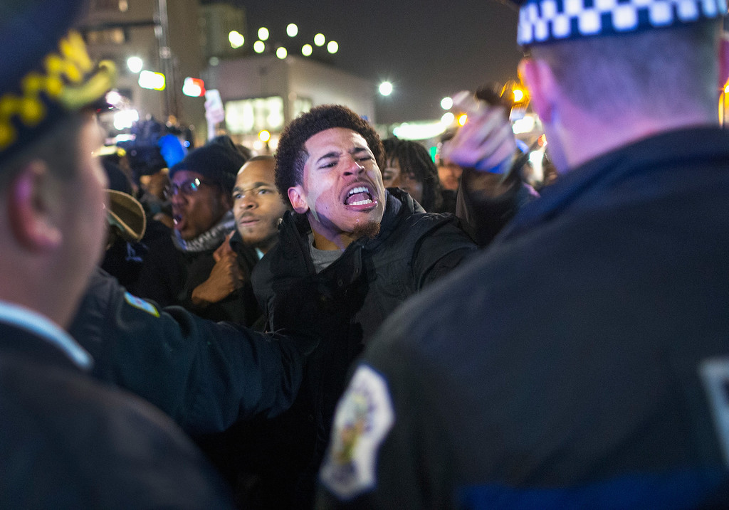 . Demonstrators confront police during a protest following the release of a video showing Chicago Police officer Jason Van Dyke shooting and killing Laquan McDonald on November 24, 2015 in Chicago, Illinois. Van Dyke was charged today with first degree murder for the October 20, 2014 shooting in which McDonald was hit with 16 bullets.  (Photo by Scott Olson/Getty Images)