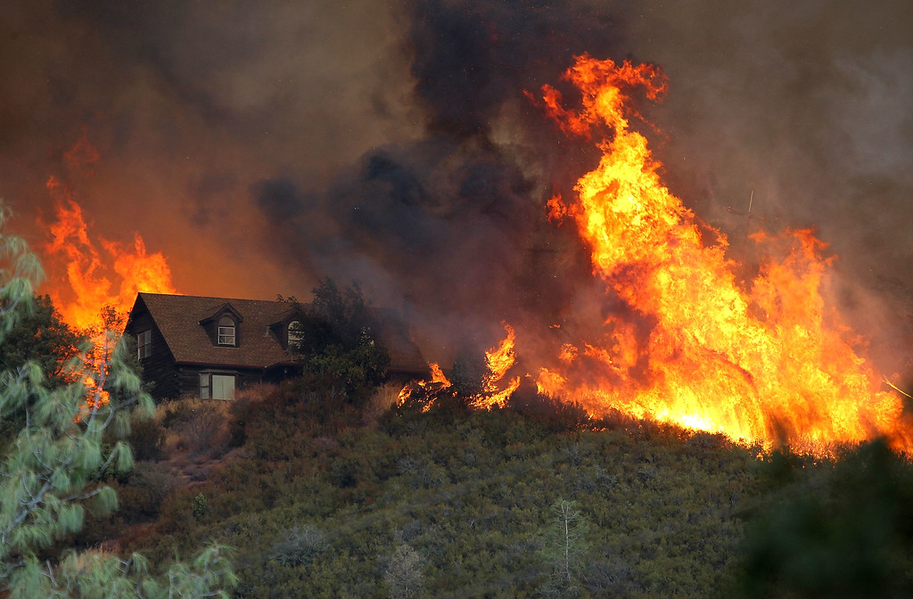 . Flames from the Rocky Fire approach a house on July 31, 2015 in Lower Lake, California. Over 900 firefighters are battling the Rocky Fire that erupted to over 15,000 acres since it started on Wednesday afternoon.  (Photo by Justin Sullivan/Getty Images)
