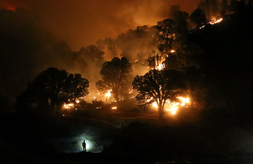 . A Cal Fire firefighter is silhouetted by his headlamp as he monitors a backfire while battling the Rocky Fire on August 3, 2015 near Clearlake, California. Nearly 3,000 firefighters are battling the Rocky Fire that has burned over 60,000 acres has forced the evacuation of 12,000 residents in Lake County. The fire is currently 12 percent contained and has destroyed at least 14 homes. 6,300 homes are threatened by the fast moving  blaze.  (Photo by Justin Sullivan/Getty Images)
