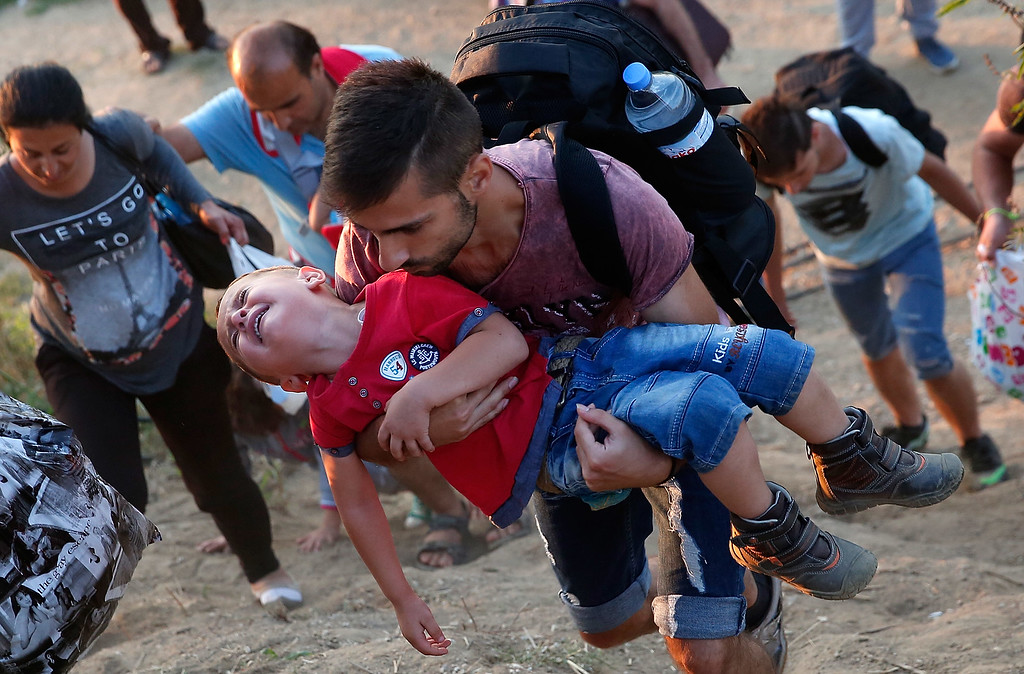 . A young Syrian boy cries as his father carries him up a steep hill as they walk to a border crossing on the Greek and Macedonian border September 3, 2015 near Idomeni, Greece. From Idomeni migrants continue north into Macedonia. Since the beginning of 2015 the number of migrants using the so-called \'Balkans route\' has exploded with migrants arriving in Greece from Turkey and then traveling on through Macedonia and Serbia before entering the EU via Hungary. The number of people leaving their homes in war torn countries such as Syria, marks the largest migration of people since World War II.  (Photo by Win McNamee/Getty Images)