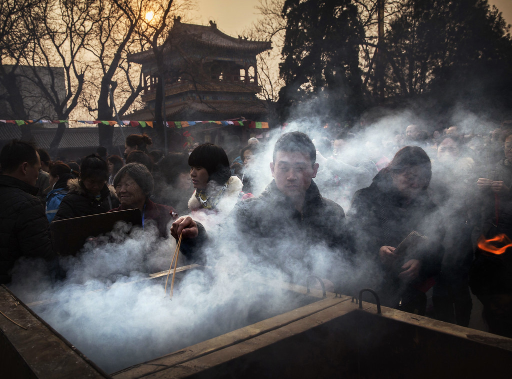 . A Chinese man is shrouded in smoke from incense as he lights a stick while praying with others at the Yonghegong Lama Temple during celebrations for the Lunar New Year February 19, 2015 in Beijing, China.The Chinese Lunar New Year of the Sheep also known as the Spring Festival, which is based on the Lunisolar Chinese calendar, is celebrated from the first day of the first month of the lunar year and ends with Lantern Festival on the Fifteenth day. (Photo by Kevin Frayer/Getty Images)