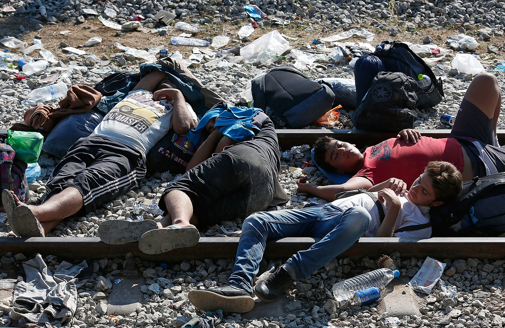 . Syrian migrants sleep on railroad tracks waiting to be processed across the Macedonian border September 2, 2015 in Idomeni, Greece. Since the beginning of 2015 the number of migrants using the so-called \'Balkans route\' has exploded with migrants arriving in Greece from Turkey and then traveling on through Macedonia and Serbia before entering the EU via Hungary. The number of people leaving their homes in war torn countries such as Syria, marks the largest migration of people since World War II.  (Photo by Win McNamee/Getty Images)