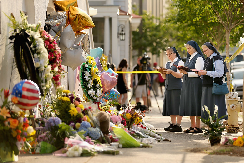 . (L-R) Sisters Margaret Kerry, Mary Thecla and Kathleen Lang of the Order of the Daughters of St. Paul pray outside the historic Emanuel African Methodist Episcopal Church June 19, 2015 in Charleston, South Carolina. South Carolina Governor Nikki Haley called for the death penalty for Dylann Storm Roof, 21, of Lexington, South Carolina, if he is found guilty of murdering nine people during a prayer meeting at the church Wednesday night. Among the dead is the Rev. Clementa Pinckney, the pastor of the church which, according to the National Park Service, is the oldest black congregation in America south of Baltimore.  (Photo by Chip Somodevilla/Getty Images)