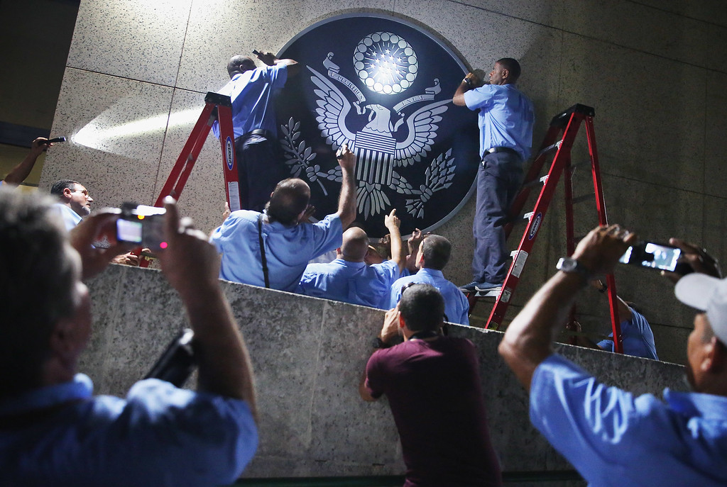 . U.S. Embassy employees hang the seal of the United States on the outside of the building a few hours before the ceremonial flag-raising August 14, 2015 in Havana, Cuba. U.S. Secretary of State John Kerry will visited Havana Friday and raised the American flag at the reopened U.S. embassy, a symbolic act after the the two former Cold War enemies reestablished diplomatic relations in July.  (Photo by Chip Somodevilla/Getty Images)
