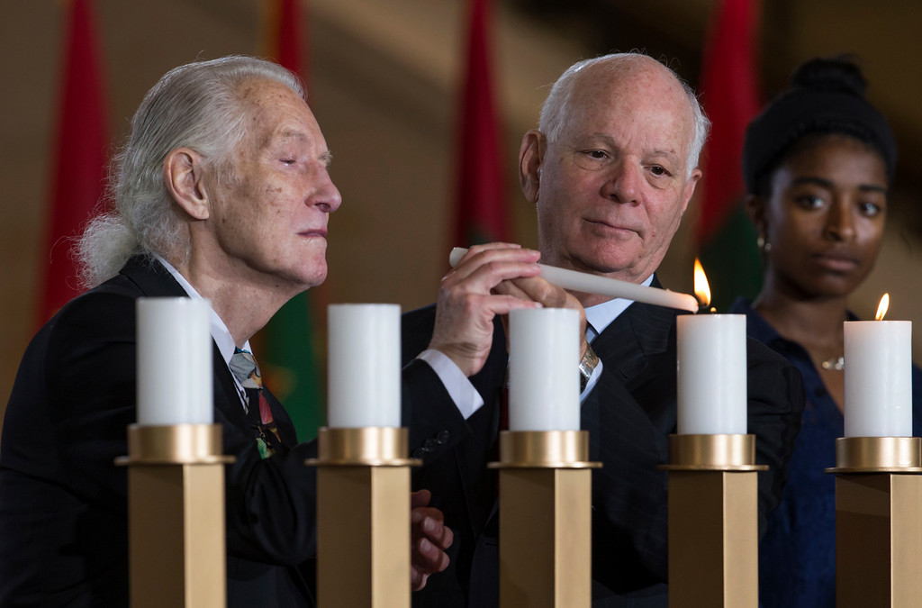 . Holocaust survivor Kurt Gutfreund, left, is assisted by Sen. Ben Cardin, D-Md., right, in lighting a candle as the U.S. Holocaust Memorial Museum holds its annual Days of Remembrance Ceremony at the U.S. Capitol to honor the victims of the Holocaust and Nazi persecution, in Washington, Thursday, May 5, 2016. Kurt Gutfreund was born in Vienna, Austria, and was sent to Theresienstadt concentration camp at age 5 with his mother. He came to the United States in 1958.  (AP Photo/J. Scott Applewhite)