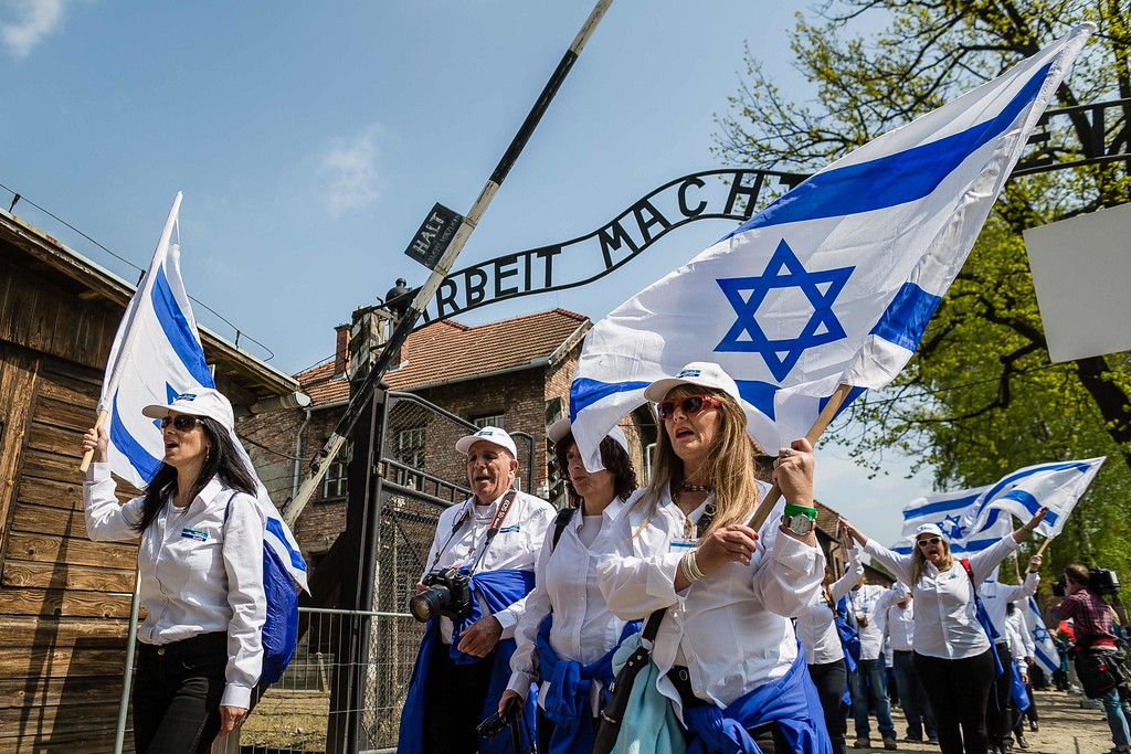 """. Participants of the annual \""""March of the Living\"""" pass the main gate of the former Nazi death camp in Oswiecim (Auschwitz), Poland, on May 5, 2016. Thousands of young Jews from 40 nations marched alongside a handful of Holocaust survivors and Polish teenagers in homage to the victims of the former Auschwitz-Birkenau WWII death camp in southern Poland. / AFP PHOTO / WOJTEK RADWANSKI/AFP/Getty Images"""