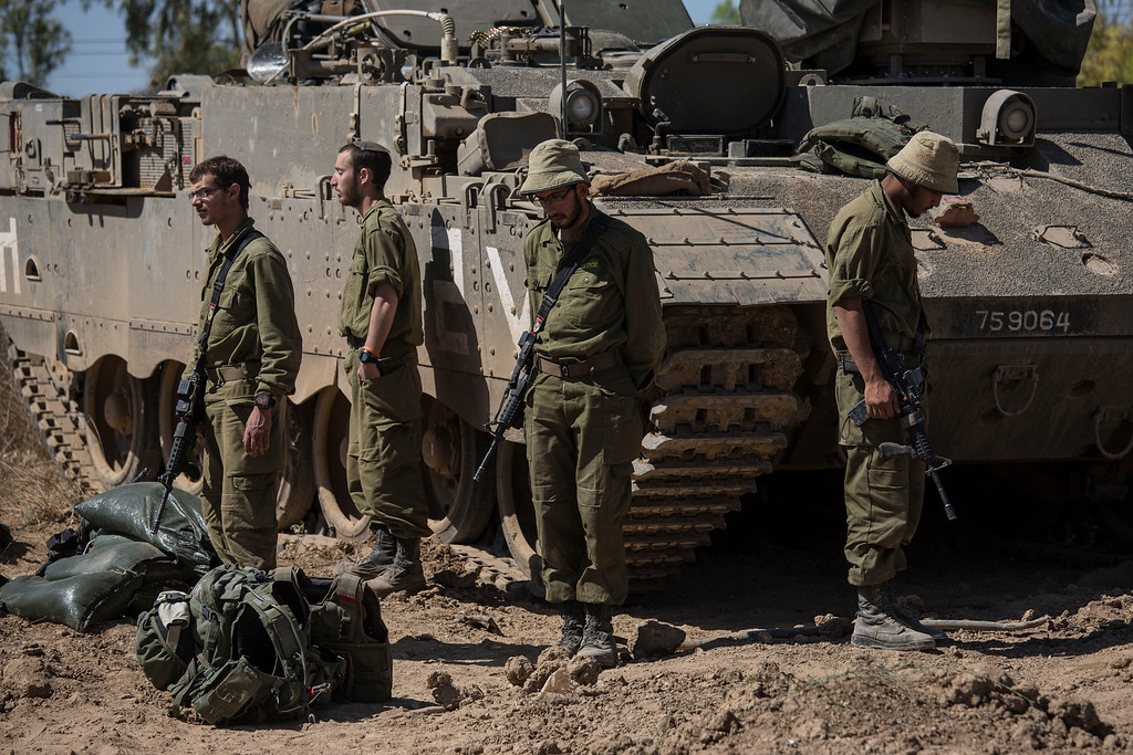 . Israeli soldiers stand in silence as sirens wailed across Israel for two minutes marking the annual Day of Remembrance for victims of the Holocaust, near the Israel Gaza border, Thursday, May 5, 2016. (AP photo/Tsafrir Abayov)