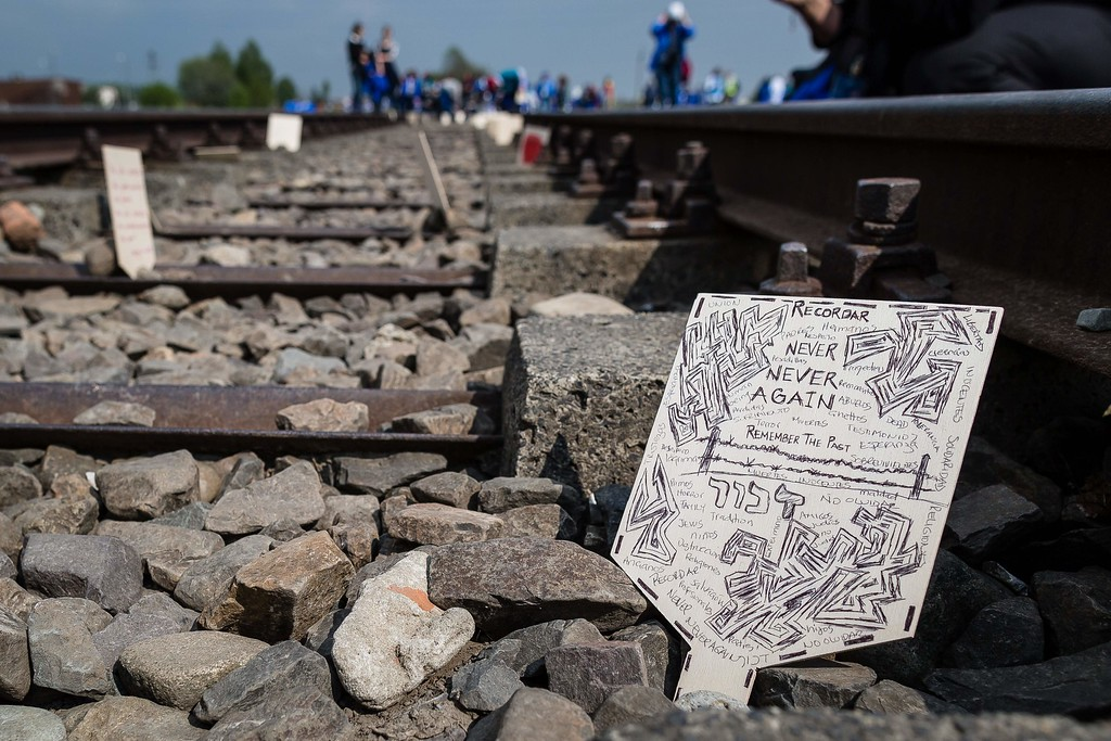 """. A wooden plaque placed by participants of the annual \""""March of the Living\"""" is seen on the rail tracks of the former Auschwitz-Birkenau Nazi death camp in Brzezinka (Birkenau) near Oswiecim (Auschwitz), Poland, on May 5, 2016. Thousands of young Jews from 40 nations marched alongside a handful of Holocaust survivors and Polish teenagers in homage to the victims of the former Auschwitz-Birkenau WWII death camp in southern Poland. / AFP PHOTO / WOJTEK  RADWANSKI/AFP/Getty Images"""