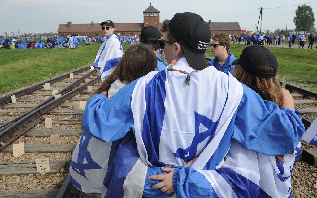 . Participants of the yearly March of the Living hug each other as they stand on the rails in the former German Nazi Death Camp Auschwitz-Birkenau, in Brzezinka, Poland, Thursday, May 5, 2016. Thousands of people from around the world have paid homage to the victims of the Holocaust with a somber march from the barracks of Auschwitz to nearby Birkenau. (AP Photo/Alik Keplicz)