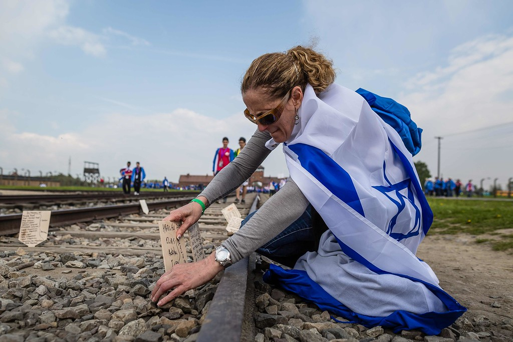 """. A woman has tied the Israeli flag around herself as she takes part in the annual \""""March of the Living\"""" at the former Nazi death camp in Oswiecim (Auschwitz), Poland, on May 5, 2016. Thousands of young Jews from 40 nations marched alongside a handful of Holocaust survivors and Polish teenagers in homage to the victims of the former Auschwitz-Birkenau WWII death camp in southern Poland. / AFP PHOTO / WOJTEK  RADWANSKI/AFP/Getty Images"""