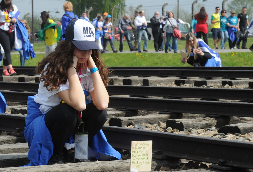 . A girl looks at a plaque she just placed on the rail tracks in the former German Nazi Death Camp Auschwitz-Birkenau during the yearly March of the Living, in Brzezinka, Poland, Thursday, May 5, 2016. Thousands of people from around the world have paid homage to the victims of the Holocaust with a somber march from the barracks of Auschwitz to nearby Birkenau(AP Photo/Alik Keplicz)