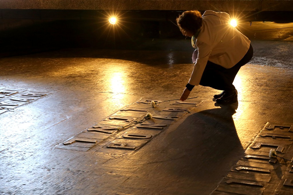 . An Israeli relative of Holocaust victims lays a flower at the Hall of Remembrance where the names of major death and concentration camps are written  during a ceremony marking the annual Holocaust Remembrance Day at the Yad Vashem Holocaust Memorial in Jerusalem on May 5, 2016. The state of Israel marks the annual Memorial Day commemorating the six million Jews murdered by the Nazis in the Holocaust during World War II. / AFP PHOTO / GALI TIBBON/AFP/Getty Images