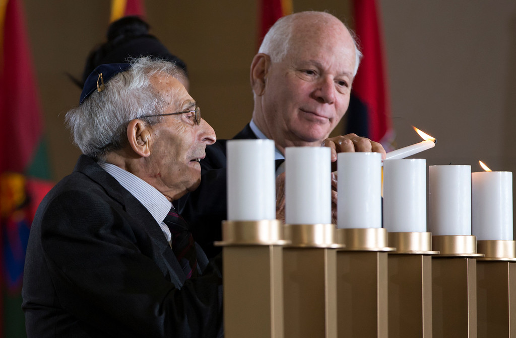 . Holocaust survivor Joseph Gringlas, left, is assisted by Sen. Ben Cardin, D-Md., right, in lighting a candle as the U.S. Holocaust Memorial Museum holds its annual Days of Remembrance Ceremony at the U.S. Capitol to honor the victims of the Holocaust and Nazi persecution, in Washington, Thursday, May 5, 2016. Gringlas, born in Poland, was sent to several forced labor camps including Birkenau before he was liberated by the Allies. He came to the United States in 1950 and now lives in Philadelphia and Boca Raton, Fla.  (AP Photo/J. Scott Applewhite)
