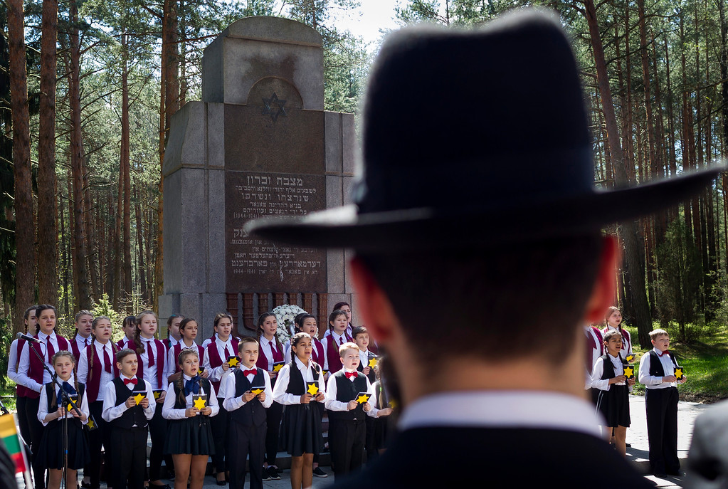 . Children sing in front of the granite Holocaust survivor memorial, during the ceremony marking Holocaust Remembrance at the Paneriai memorial in Vilnius, Lithuania, Thursday, May 5, 2016. Between July 1941 and August 1944, approximately 100,000 people of whom over half were Jewish were murdered at the site by the Nazis and a group of Lithuanians from organizations such as the Vilnius Special Squad. (AP Photo/Mindaugas Kulbis