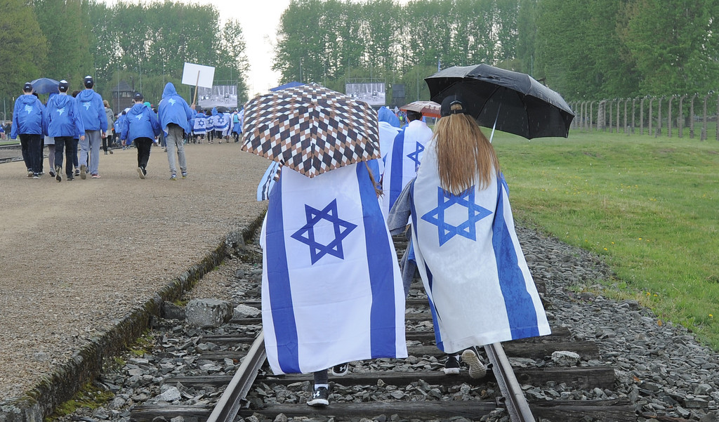 . Participants of the yearly March of the Living walk along the rails during a rainfall in the former German Nazi Death Camp Auschwitz-Birkenau, in Brzezinka, Poland, Thursday, May 5, 2016. Thousands of people from around the world have paid homage to the victims of the Holocaust with a somber march from the barracks of Auschwitz to nearby Birkenau. (AP Photo/Alik Keplicz)