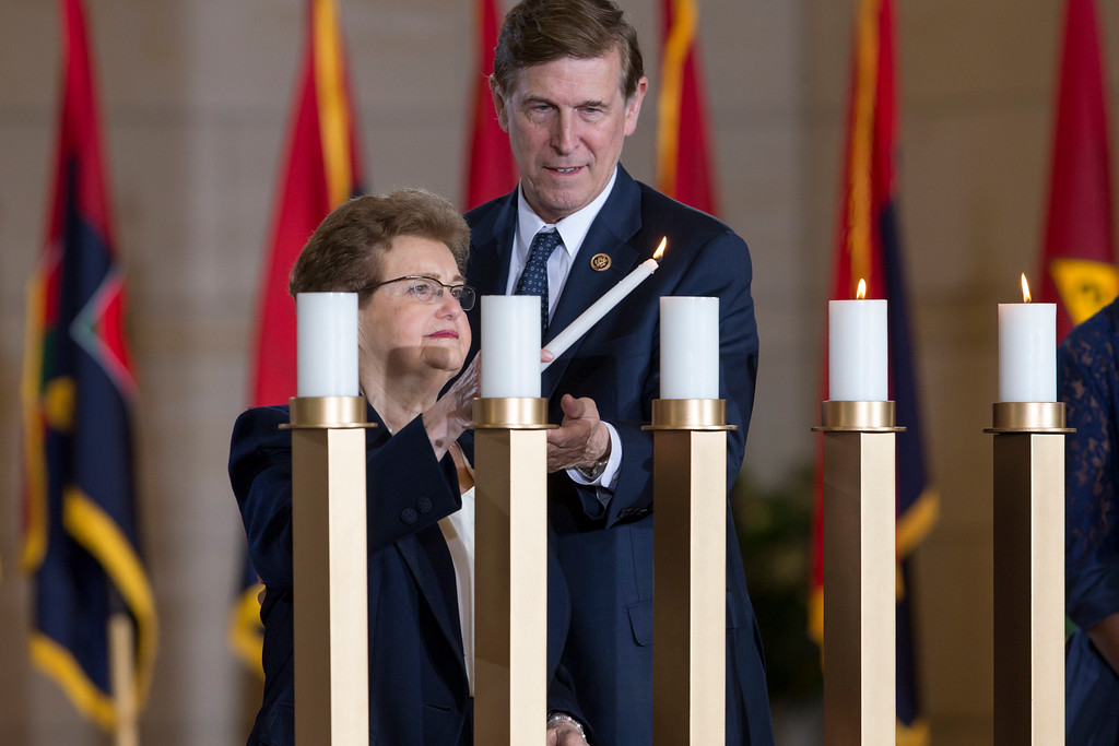 . Holocaust survivor Rose Reichbach, left, is assisted by Rep. Don Beyer D-Va., right, in lighting a candle as the U.S. Holocaust Memorial Museum holds its annual Days of Remembrance Ceremony at the U.S. Capitol to honor the victims of the Holocaust and Nazi persecution, in Washington, Thursday, May 5, 2016. Rose Reichbach and her family fled from their native Poland to Belarus  during the Nazi invasion. She and her parents were sent to gulags in Siberia and later to Kyrgyzstan. After the war, she immigrated to Israel and later settled in Washington, DC.   (AP Photo/J. Scott Applewhite)