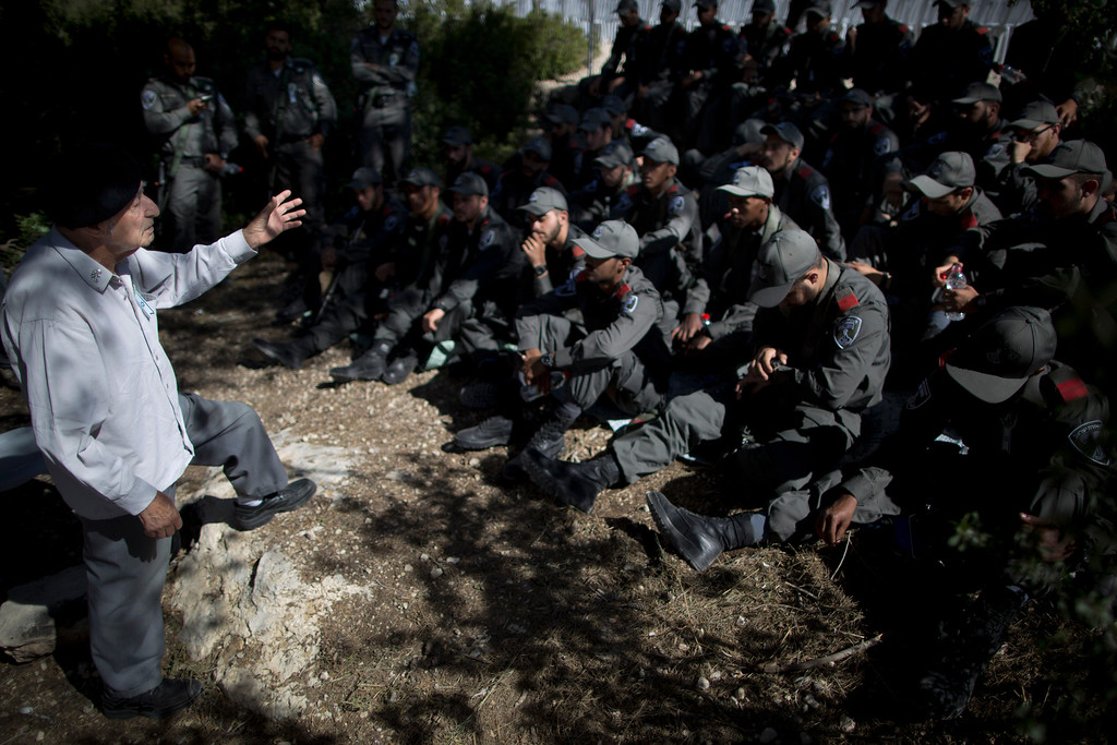 . Holocaust survivor Ezer Lev Zion, 91, left, tells his personal testimony to Israeli border police officers, during a ceremony marking the annual Holocaust remembrance day in the Martyr\'s forest near Moshav Kesalon, in central Israel, Thursday, May 5, 2016. Sirens sounded across Israel on Thursday morning, bringing life to a standstill as millions of Israelis observed a moment of silence to honor the memory of the 6 million Jews killed in the Nazi Holocaust during World War II. (AP Photo/Oded Balilty)