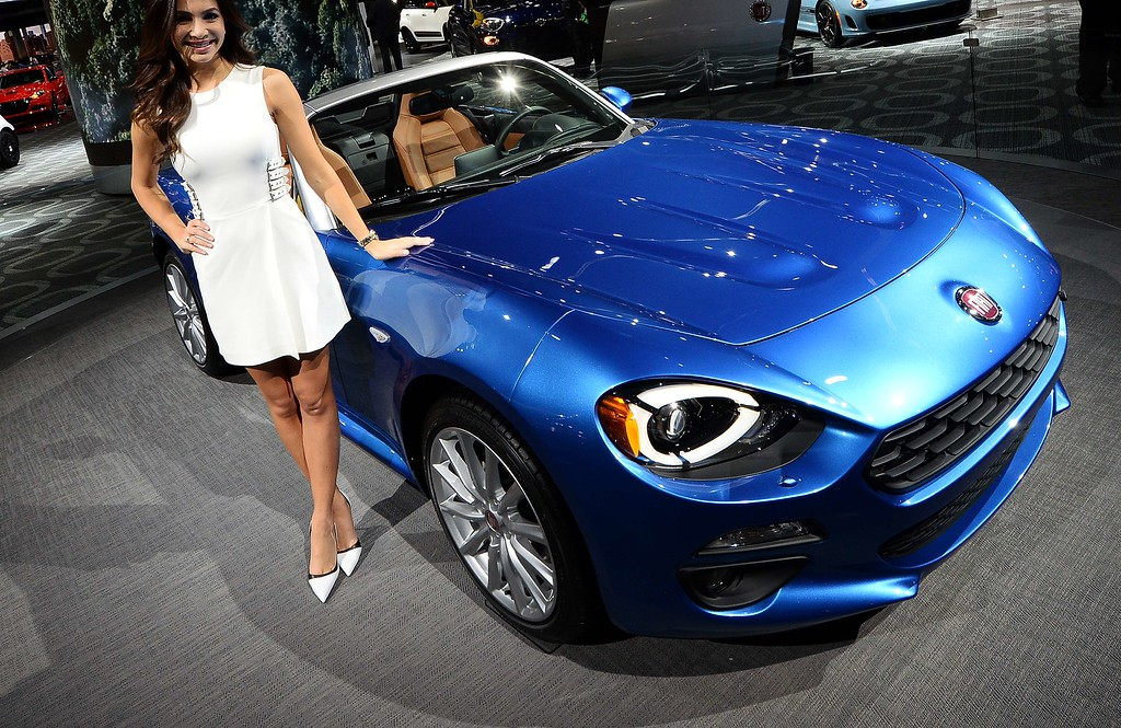 . A model poses next to the 2016 Fiat 124 Spider during the press preview of the 2016 North American International Auto Show in Detroit, Michigan, on January 12, 2016. AFP PHOTO/JEWEL SAMAD/AFP/Getty Images