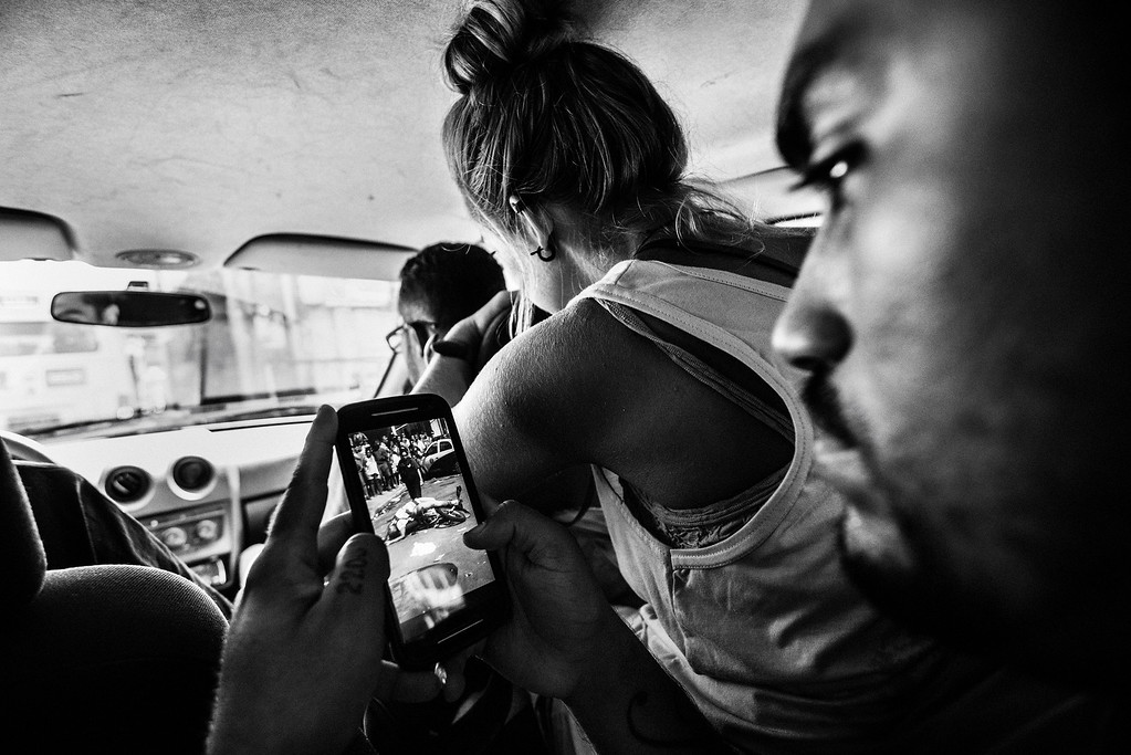 ". In this image released by World Press Photo titled ""Citizen Journalism in Brazil\'s Favelas\"" by photographer Sebastian Liste for Noor agency which won third prize in the Daily Life Stories category shows the leader of the Papo Reto collective receiving an image of a 22-year-old taxi driver who was shot dead by a police officer, Rio de Janeiro, Brazil, Feb. 8, 2015. A group of friends from Alemao, a slum in Rio de Janeiro, formed a media collective called Papo Reto, or \""straight talk\"". Social media allow them to report stories from their community otherwise ignored by traditional media. (Sebastian Liste/Noor, World Press Photo via AP)"