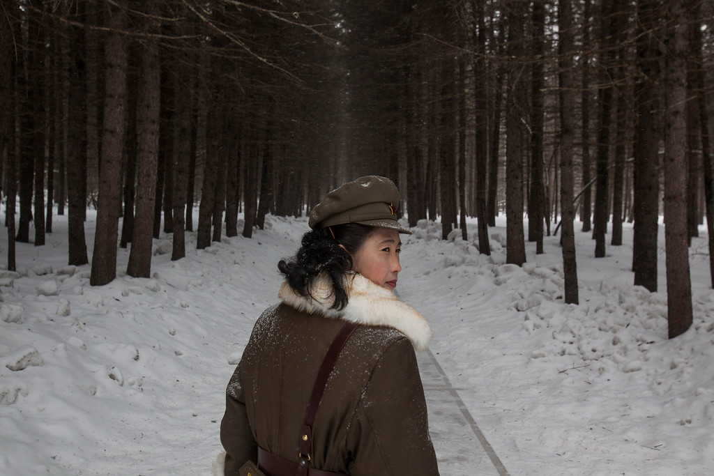 ". In this image released by World Press Photo titled ""North Korea Life in the Cult of Kim, by photographer David Guttenfelder, AP, which won a third prize in the Long term Projects category shows a North Korean soldier, working as a guide, walking through a forest April 4, 2012, that is said to be a former camp site where the late North Korean leader Kim Il Sung overnight while leading a battle against the Japanese at the foot of Mount Paektu, North Korea. (David Guttenfelder/AP, World Press Photo via AP)"