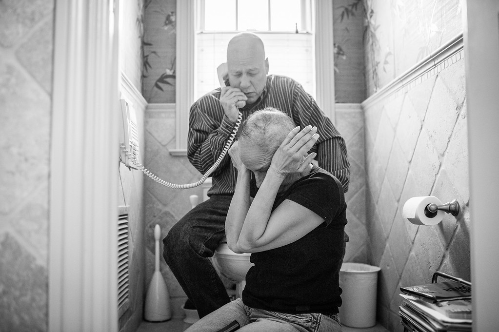 ". In this image released by World Press Photo titled ""A Life in Death\"" by photographer Nacy Borowick which won second prize Long Term Projects shows Howie and Laurel Borowick sitting next to the bathroom telephone as they receive the most recent news from their oncologist. New York, US, March 8, 2013. A daughter photographs her own parents who were in parallel treatment for stage-four cancer, side by side. The project looks at love, life, and living, in the face of death. It honors their memory by focusing on their strength and love, both individually and together, and shares the story of their final chapters, within a year of each other. (Nancy Borowick, World Press Photo via AP)"