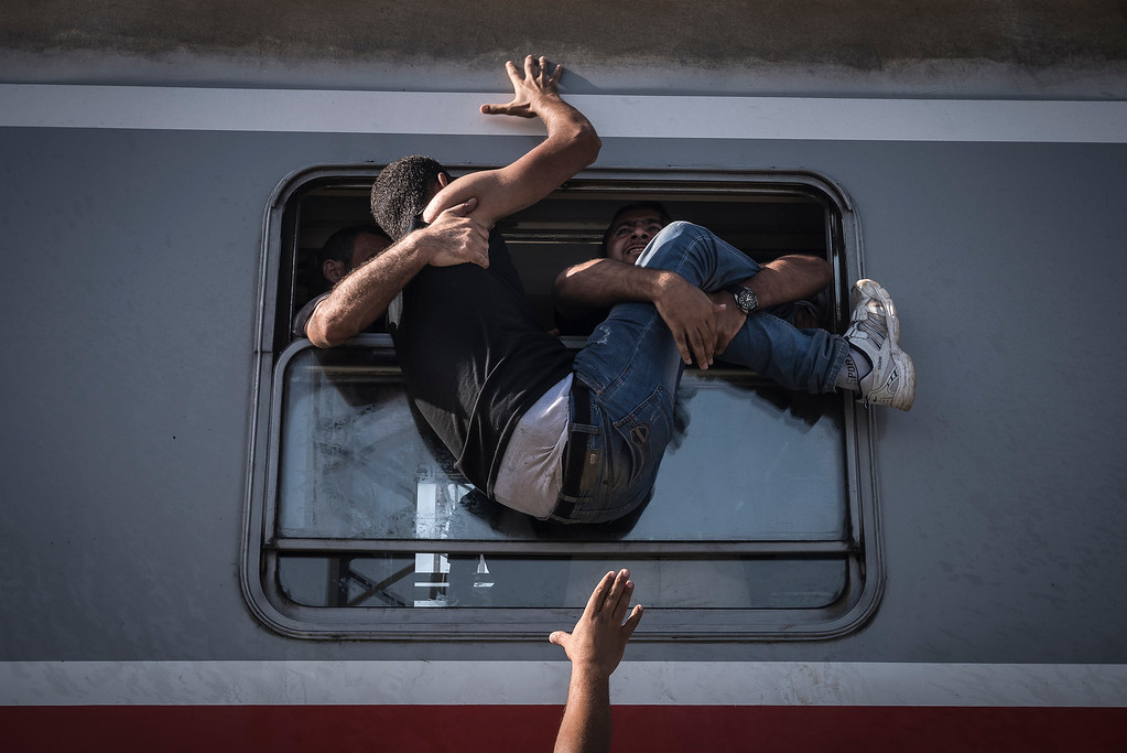 ". In this image released by World Press Photo titled ""Reporting Europe\'s Refugee Crisis\"" by photographer Sergey Ponomarev for The New York Times which won the first prize in the General News Stories category shows refugees attempting to board a train headed to Zagreb, Croatia in Tovarnik, Croatia, 18 September 2015. (Sergey Ponomarev for The New York Times, World Press Photo via AP)"