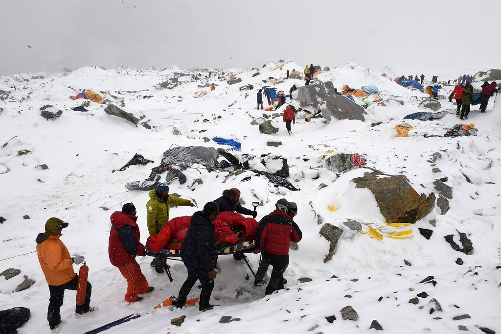 . This file photo taken by Agence France-Presse (AFP)photographer Roberto Schmidt on April 25, 2015 shows rescuers using a makeshift stretcher to carry an injured person after an avalanche triggered by an earthquake flattened parts of Everest Base Camp.     AFP\'s veteran lensman Roberto Schmidt on February 18, 2016 won second prize at the prestigious World Press Photo Award in the Spot News stories category, for his dramatic shots of the deadly avalanche on Mount Everest triggered by last April\'s Nepal earthquake. / AFP / ROBERTO SCHMIDT/AFP/Getty Images