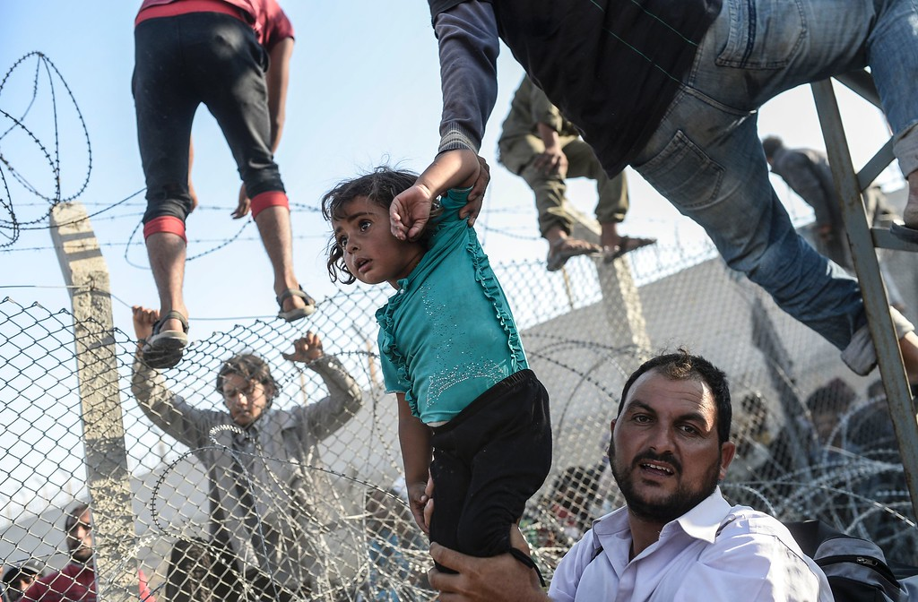 . This file photo taken by Agence France-Presse (AFP) photographer on June 14, 2015 shows a Syrian child fleeing the war being lifted over border fences to enter Turkish territory illegally, near the Turkish border crossing at Akcakale in Sanliurfa province.  Turkey-based Bulent Kilic on February 18, 2016 won third prize in the Spot News stories category at the prestigious World Press Photo Award for his pictures of Syrian refugees on the Turkish border, highlighting Europe\'s worst migrant crisis since World War II. / AFP / BULENT KILICBULENT KILIC/AFP/Getty Images