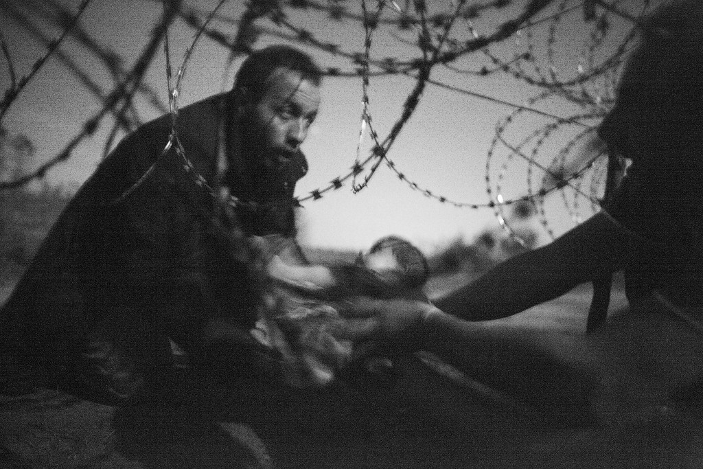 ". In this image released by World Press Photo shows the World Press Photo of the Year titled ""Hope for a new Life\"" by photographer Warren Richardson. The picture also won a first prize in the Spot News singles category and shows a man passing a baby through the fence at the Serbia-Hungary border in Roszke, Hungary, Aug. 28, 2015. (Warren Richardson, World Press Photo via AP)"
