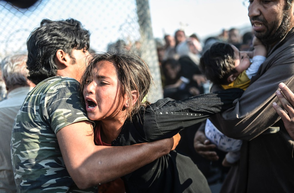 . This file photo taken by Agence France-Presse(AFP ) photographer Bulent Kilic on June 14, 2015 shows Syrians fleeing the war rushing through broken down border fences to enter Turkish territory illegally, near the Turkish border crossing at Akcakale in Sanliurfa province.    Turkey-based Bulent Kilic on February 18, 2016 won third prize in the Spot News stories category at the prestigious World Press Photo Award for his pictures of Syrian refugees on the Turkish border, highlighting Europe\'s worst migrant crisis since World War II. / AFP / BULENT KILICBULENT KILIC/AFP/Getty Images