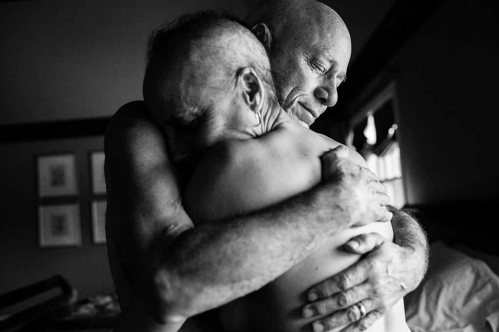 ". In this image released by World Press Photo titled ""A Life in Death\"" by photographer Nacy Borowick which won second prize Long Term Projects shows Howie and Laurel Borowick embrace in the bedroom of their home. In their 34- year marriage, they were diagnosed with stage-four cancer at the same time. New York, USA, March 8, 2013. A daughter photographs her own parents who were in parallel treatment for stage-four cancer, side by side. The project looks at love, life, and living, in the face of death. It honors their memory by focusing on their strength and love, both individually and together, and shares the story of their final chapters, within a year of each other. (Nancy Borowick, World Press Photo via AP)"