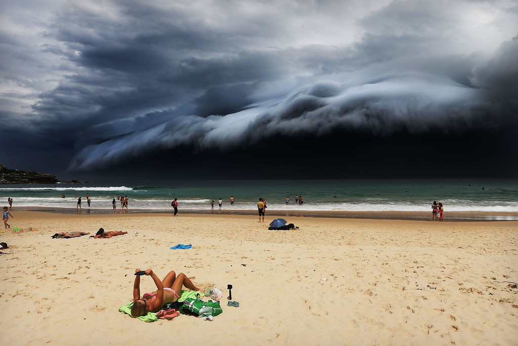 ". In this image released by World Press Photo titled ""Storm Front on Bondi Beach\"" by photographer Rohan Kelly for the Daily Telegraph which won first prize in the Nature singles category shows a massive cloud tsunami looming over Sydney as a sunbather reads, oblivious to the approaching cloud on Bondi Beach, Sydney, Australia, Nov. 6, 2015. (Rohan Kelly/Daily Telegraph, World Press Photo via AP)"