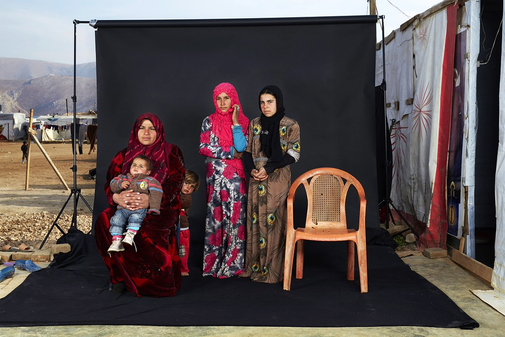 ". In this image released by World Press Photo titled ""Lost Family Portraits\"" by photographer Dario Mitidieri which won third prize in the People singles category shows a portrait of a Syrian refugee family in a camp in Bekaa Valley, Lebanon, on Dec. 15, 2015. The empty chair in the photograph represents a family member who has either died in the war or whose whereabouts are unknown. (Dario Mitidieri, World Press Photo via AP)"