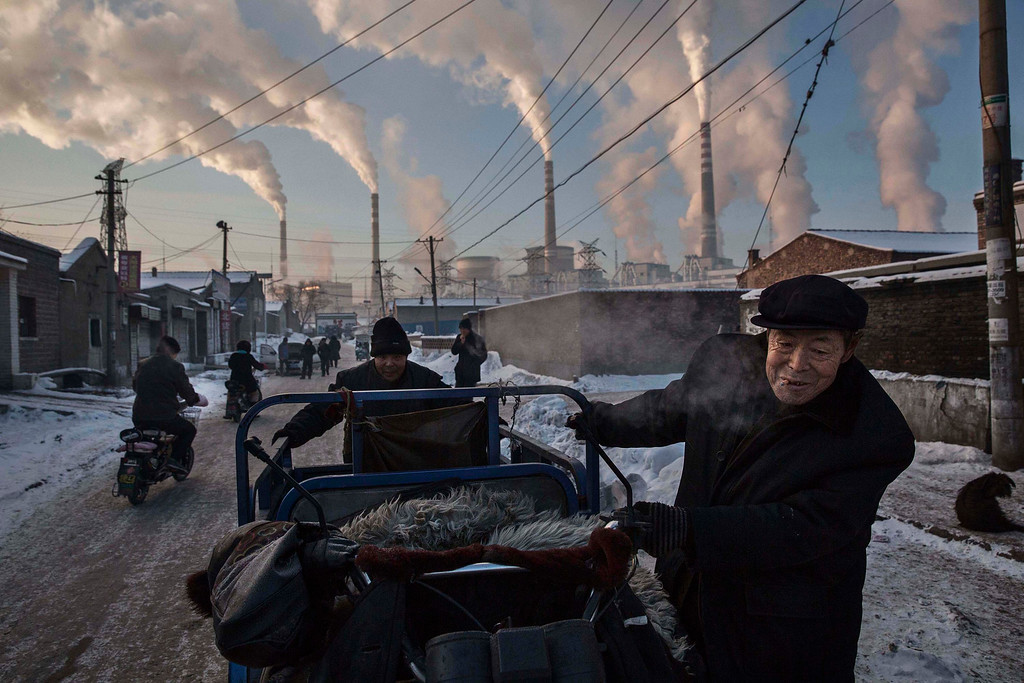 ". In this image released by World Press Photo titled ""China\'s Coal Addiction\"" by photographer Kevin Frayer for Getty Images which won first prize in the Daily Life singles category shows Chinese men pulling a tricycle in a neighborhood next to a coal-fired power plant in Shanxi, China, on Nov. 26, 2015. A history of heavy dependence on burning coal for energy has made China the source of nearly a third of the world\'s total carbon dioxide (CO2) emissions, the toxic pollutants widely cited by scientists and environmentalists as the primary cause of global warming. (Kevin Frayer/Getty Images, World Press Photo via AP)"