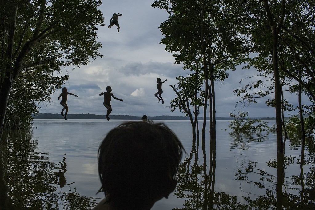 ". In this image released by World Press Photo titled ""Amazon\'s Munduruku Tribe\"" by photographer Mauricio Lima for The New York Times which won second prize in the Daily Life singles category shows indigenous Munduruku children playing in the Tapajos river in the tribal area of Sawre Muybu, Itaituba, Brazil, Feb. 10, 2015. The tribesmen of the Munduruku, who for centuries have sanctified the Tapajos River on which their villages sit, are fighting for survival. Brazil�s government plans to flood much of their land to build a $9.9 billion hydroelectric dam, the Sao Luiz do Tapajos, as part of a wider energy strategy across the Amazon rainforest. (Mauricio Lima/The New York Times, World Press Photo via AP)"