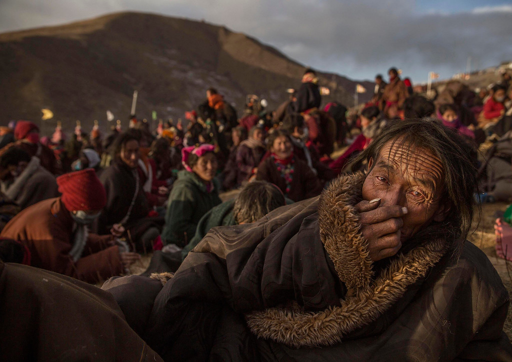 ". In this image released by World Press Photo titled ""Bliss Dharma Assembly\"" by photographer Kevin Frayer for Getty Images which won second prize in the Daily Life stories category shows Tibetan Buddhist nomads listening during the annual Bliss Dharma Assembly in Sertar county, Garze Tibetan Autonomous Prefecture, Sichuan province, China, Oct. 31, 2015. (Kevin Frayer/Getty Images, World Press Photo via AP)"